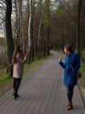 Twee gelukkige jonge meisjes ontmoetten elkaar in het park Vrouwelijke vriendschap Gang in het park in openlucht Royalty-vrije Stock Foto's