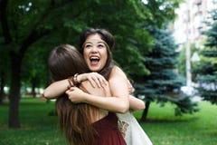 Twee gelukkige jonge meisjesomhelzing elkaar in de zomerpark stock afbeelding