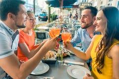 Twee gelukkige jonge paren die terwijl het zitten samen bij restaurant roosteren royalty-vrije stock afbeelding