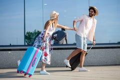 Twee gelukkige jonge toeristen die handen houden en voor een luchthaventerminal lopen royalty-vrije stock fotografie