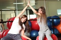 Twee gelukkige jonge vrouwen in de gymnastiek royalty-vrije stock afbeelding