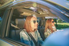 Twee gelukkige jonge vrouwen die in auto reizen royalty-vrije stock afbeeldingen