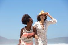 Twee gelukkige jonge vrouwen die bij het strand samen lopen Stock Foto
