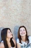 Twee gelukkige jonge vrouwen die omhoog op exemplaarruimte kijken Stock Afbeelding
