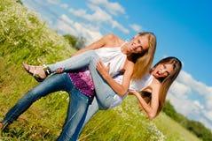 Twee gelukkige jonge vrouwen die pret hebben in openlucht stock fotografie