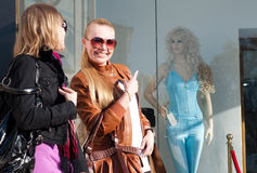 Twee gelukkige jonge vrouwen die samen met het winkelen zakken lopen stock foto's