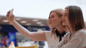 Twee gelukkige jonge vrouwen die selfie in de wandelgalerij maken stock video