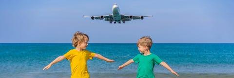 Twee gelukkige jongens hebben pret op het strand lettend op de landende vliegtuigen Het reizen op een vliegtuig met jonge geitjes stock foto