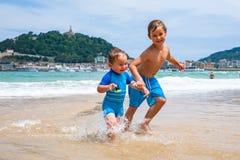 Twee gelukkige jongens in het lopen langs een strand die grote plonsen maken Royalty-vrije Stock Foto's