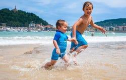 Twee gelukkige jongens in het lopen langs een strand die grote plonsen maken Royalty-vrije Stock Foto