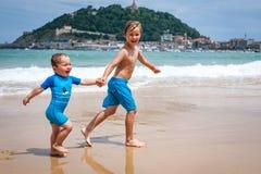 Twee gelukkige jongens in het lopen langs een strand die grote plonsen maken Stock Fotografie