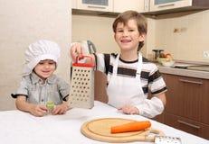 Twee gelukkige jongens in keuken Stock Afbeelding