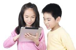 Twee gelukkige kinderen die de computer van het aanrakingsstootkussen met behulp van Royalty-vrije Stock Fotografie
