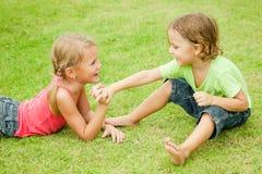 Twee gelukkige kinderen die op het gras spelen Stock Fotografie