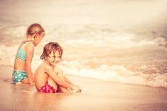 Twee gelukkige kinderen die op het strand spelen Stock Foto's