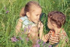 Twee gelukkige kinderen die in park spelen Stock Afbeeldingen