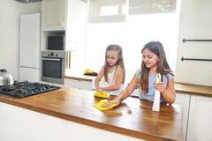 Twee gelukkige kleine zusters die keukenlijst schoonmaken stock foto's