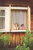 Twee gelukkige leuke meisjes die pret in venster thuis in zonnige dag hebben Stock Foto's