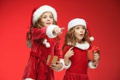 Twee gelukkige meisjes in de hoeden van de Kerstman met giftdozen bij studio Royalty-vrije Stock Foto's