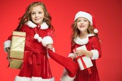 Twee gelukkige meisjes in de hoeden van de Kerstman met giftdozen bij studio Stock Foto