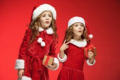Twee gelukkige meisjes in de hoeden van de Kerstman met giftdozen bij studio Royalty-vrije Stock Fotografie