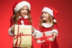 Twee gelukkige meisjes in de hoeden van de Kerstman met giftdozen bij studio Stock Afbeeldingen