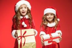 Twee gelukkige meisjes in de hoeden van de Kerstman met giftdozen bij studio Stock Fotografie