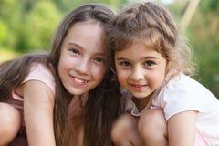 Twee Gelukkige meisjes die bij het de zomerpark koesteren stock fotografie