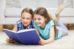 Twee gelukkige meisjes die boek thuis lezen Stock Fotografie