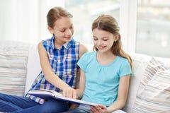 Twee gelukkige meisjes die boek thuis lezen Stock Afbeeldingen
