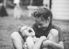 Twee Gelukkige meisjes die en bij het de zomerpark lachen koesteren stock afbeeldingen