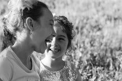 Twee Gelukkige meisjes die en bij het de zomerpark lachen koesteren royalty-vrije stock afbeeldingen