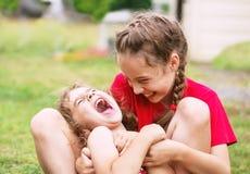 Twee Gelukkige meisjes die en bij het park omhelzen lachen stock fotografie