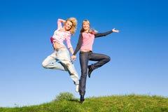 Twee gelukkige meisjes die op groene weide springen Royalty-vrije Stock Foto's