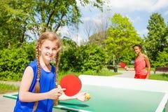 Twee gelukkige meisjes die pingpong buiten spelen royalty-vrije stock afbeeldingen