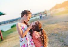 Twee Gelukkige meisjes die pret hebben en bij weide bij su omhelzen royalty-vrije stock afbeeldingen