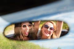 Twee gelukkige meisjes in een autoachteruitkijkspiegel stock foto