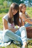 Twee gelukkige meisjes op picknick Stock Afbeeldingen