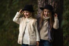 Twee gelukkige meisjes zijn even gekleed: in bontvesten en hoeden in de bos Kleine meisjes in park Stock Afbeelding
