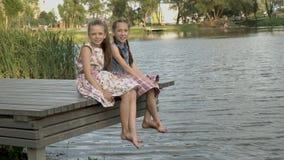 Twee gelukkige meisjes zitten op de Bank van de rivier in het stadspark op een de zomeravond op een houten brug bij stock footage