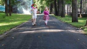 Twee gelukkige meisjesgang met windmolens in park stock video