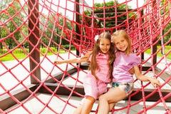 Twee gelukkige meisjesomhelzing op rode kabels van speelplaats Royalty-vrije Stock Foto's