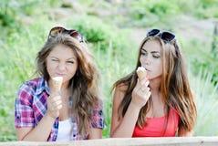 Twee gelukkige meisjesvrienden die roomijs in openlucht eten Royalty-vrije Stock Fotografie