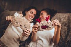 Twee gelukkige meisjesvrienden liggen in bed en dragen thuis slaapmasker dichtbij Kerstmisboom in comfortabel binnenland royalty-vrije stock fotografie