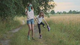 Twee gelukkige meisjeszusters die na regen in het vuile klerenkinderen spreken lopen die, pret gietend water van hun laarzen lach stock videobeelden