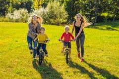Twee gelukkige moeders onderwijzen hun gelukkige zonen om een fiets te berijden stock afbeelding