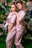 Twee gelukkige mooie blonden in sexy gestreepte pyjama's en hielen op een bloemachtergrond _zij be*vinden achter elkaar en kijken stock foto