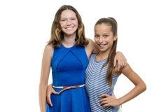 Twee gelukkige mooie jonge meisjesvrienden die, met perfecte witte die glimlach omhelzen, op witte achtergrond wordt geïsoleerd stock foto's