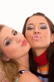 Twee gelukkige mooie meisjes die over wit worden geïsoleerdm Stock Afbeeldingen
