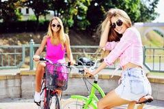 Twee gelukkige mooie meisjes op fietsen Royalty-vrije Stock Afbeelding